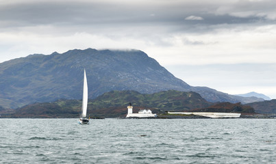 Panoramic view of the cliffs, mountains and valleys of the islands of Inner Hebrides on a cloudy day. Scotland, UK. White sloop  rigged yacht and old loghthouse close-up