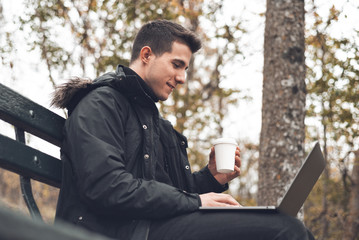 Young man drinking coffee with laptop in autumn park outdoors. Man with laptop and coffee in autumn park under fall foliage .