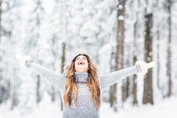 Young, beautiful woman with winter cap and gray sweater and closed eyes in winter landscape