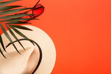 Summer vacation concept. Men's hat, sunglasses and palm branch on a bright, coral background
