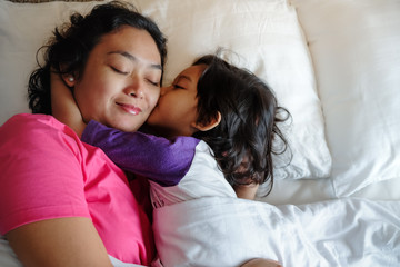 Southeast Asian Boy Showing His Love, Hugging and Kissing His Mother while Still on Bed In The Morning. Asian Ethnicity Domestic Lifestyle