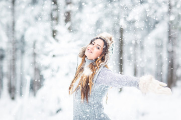 Young, beautiful,happy woman with winter cap and gray sweater and closed eyes in winter landscape