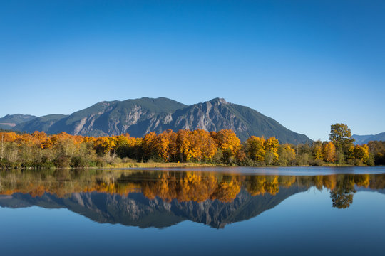 The calm, still waters of a large pond near Snoqualmie, Washington, reflect the beautiful fall colors of shoreline trees and Mt. Si in the distant background. 16 x 9 crop.