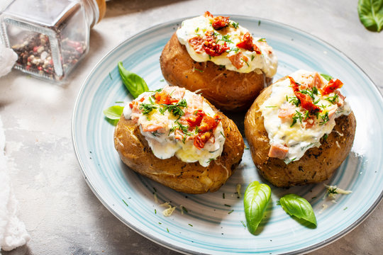 Baked stuffed potatoes with bacon, tomato, cheese on concrete background.