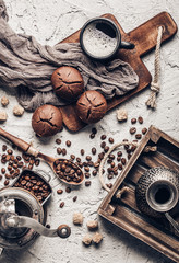 Wall Mural - Coffee beans with coffee and muffins on grey textured background.