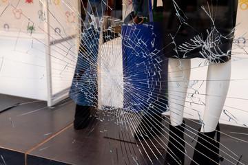 Fototapeta Shattered window of broken storefront store crack from impact on shop glass boutique obraz