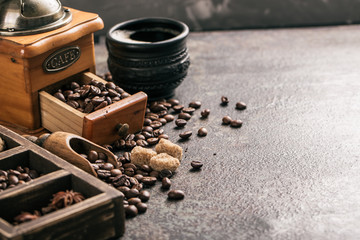 Wall Mural - Coffee with coffee grinder and coffee beans on dark textured background.