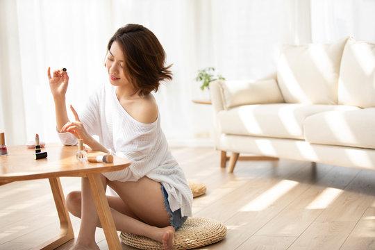 Young Chinese woman applying nail polish at home