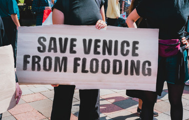 "The phrase "" Save Venice from flooding "" drawn on a carton banner. A girl holds a cardboard with an inscription. Girls on the street. Flooding. Climate change. Cataclysm"
