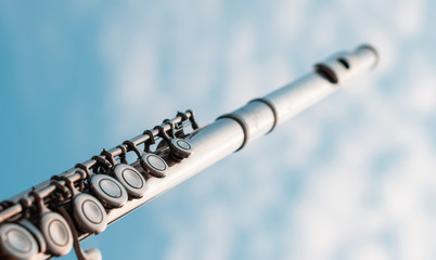 Detail of silver flute key shining by sunset light with cloudy blue sky background, Elegant metal woodwind instrument for music student education