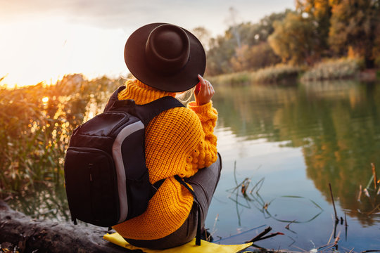 Traveler with backpack relaxing by autumn river at sunset. Young woman admires nature