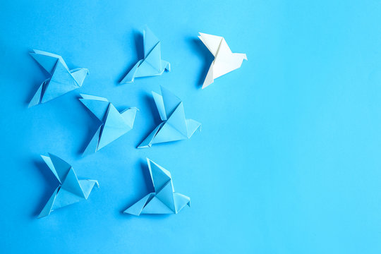 White origami bird among blue ones on color background. Concept of uniqueness