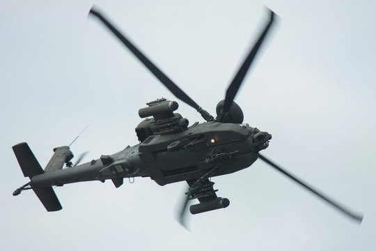 Apache helicopter turning blurred rotors underside view