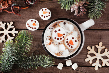 Hot chocolate with snowman marshmallows. Top view table scene with Christmas decor against a dark wood background.
