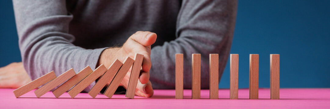 Man stopping dominos on pink surface from collapsing