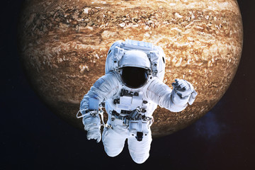 Astronaut close to the fantastic far brown rock planet. Science fiction. Elements of the image are furnished by NASA