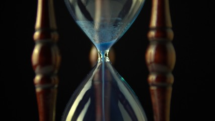 Tuinposter Ikea Extreme close up view of sand flowing through an hour glass. Super closeup of hourglass clock middle. Classic sandglass timer countdown.