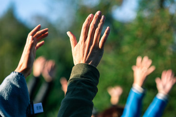 Selective focus photo of group of people standing outside while holding their arms and hands up in the air