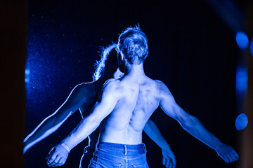 Backside view photo of bare chested adult man and woman standing against each other with their arms both spread