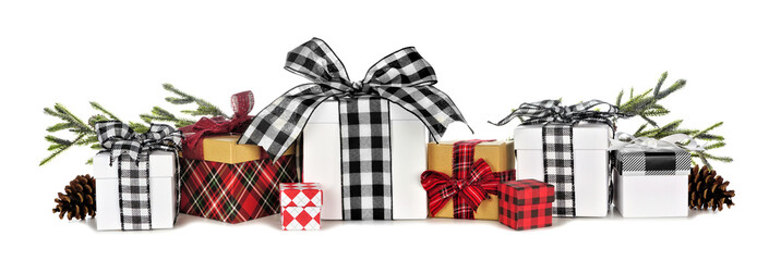 Assortment of many Christmas gift boxes with plaid wrap and ribbon and tree branches isolated on a...