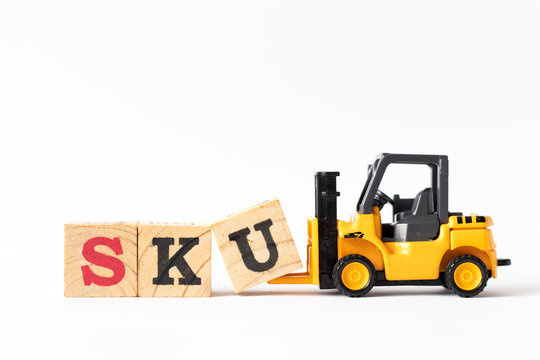 Toy forklift hold wood letter block U to complete word SKU (abbreviation of stock keeping unit) on white background