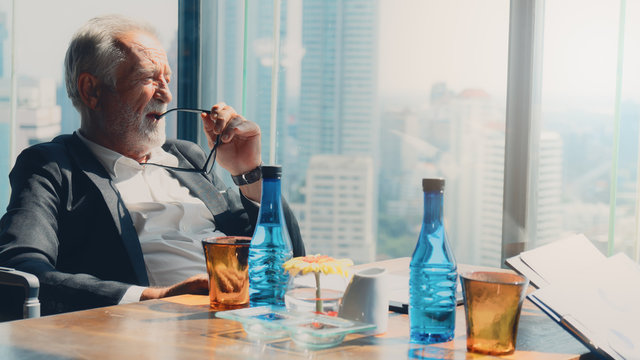 senior executive sitting by office window thinking of business strategy of company
