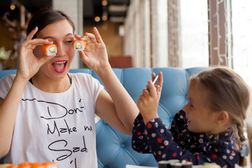 Funny mom holds sushi rolls in front of her eyes. Little girl takes pictures of her