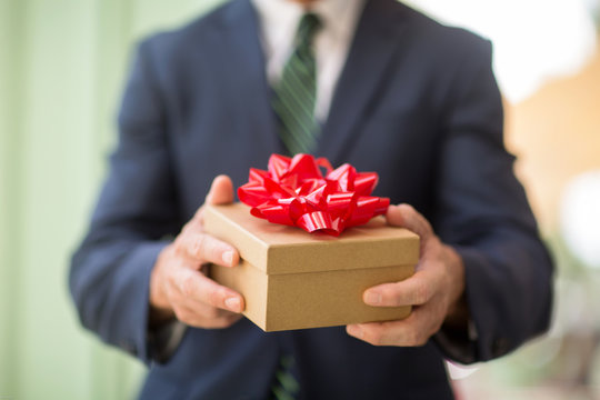 Unrecognizable  businessman holding a present.