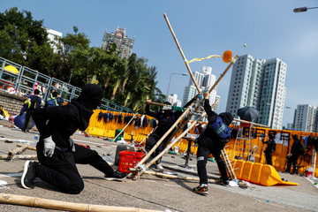 Student protesters use an improvised slingshot to fling tennis balls across a barricade as leisure at Hong Kong Baptist University, Hong Kong