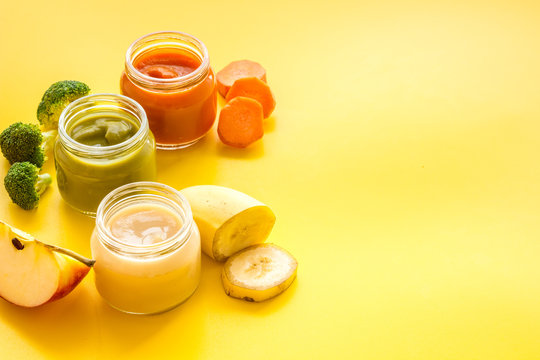 Baby food. Colorful puree in glass jars near vegetables and fruits on yellow background space for text