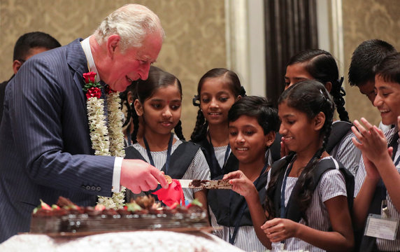 Britain's Prince Charles shares a candid moment with children from a school after cutting a cake on his birthday in Mumbai