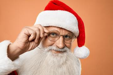 Portrait of senior kind Santa Claus holding hand on glasses