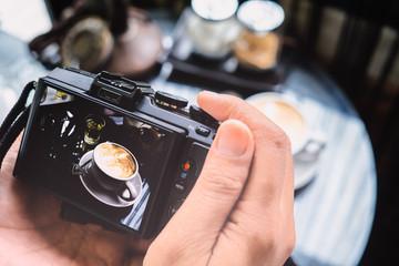 Photography blogging workshop concept. Hand holding camera takin