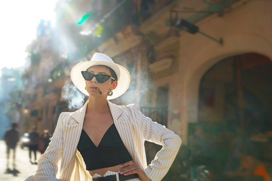 Stylish woman in a white suit and white hat smokes a cigar on a city street