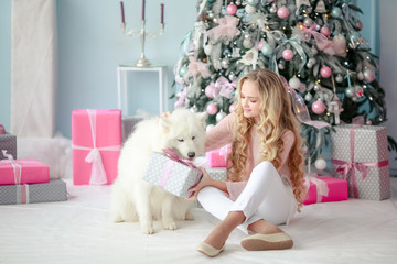 A girl sits with her dog surrounded by New Year's gifts under a Christmas tree in a photo studio.