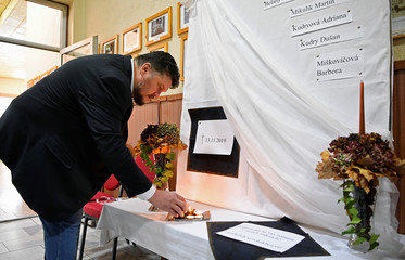 Mayor of Kolinany Robert Balko lights a candle at a makeshift memorial for the victims of a bus that crashed near the city of Nitra, at the municipal office in Kolinany
