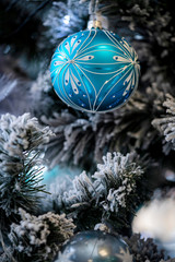 Christmas background. Detail view of blue and silver baubles and festive decorations hanging on a white christmas tree.