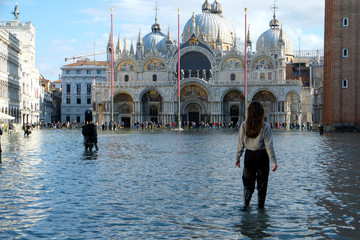 People walk in the flooded St. Mark's Square during a period of seasonal high water in Venice