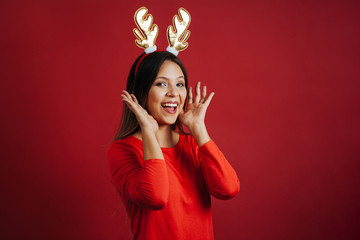 Surprised woman with christmas reindeer horns headband over red background