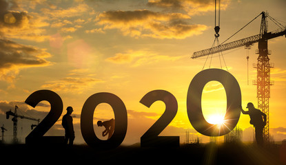 Silhouette of engineer and construction team work constructively to create.  huge figures 2020 at the construction site, Concept Happy new year next good year.