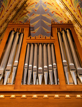Pipe organ frontal shot, shiny silver prospect pipes pattern, row closeup. Sacral music, church musical service and classical organ concert poster concept. Old pipe organ in a small wooden church