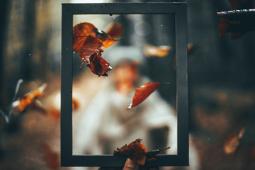 Girl throwing leaves through a picture frame