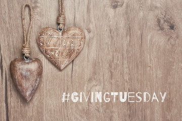 Giving Tuesday, global day of charitable giving. Give help, donations and support. Wooden hearts, flat lay on wood with text. Givingtuesday is a global charity campaign - Black Friday of Charity.