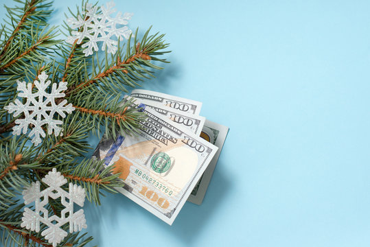 dollars and snowflakes on fir branches on blue winter background with copy space. christmas gift
