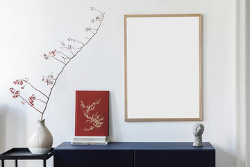 Stylish scandinavian interior design with mock up picture frames, navy blue commode, flowers in vase, books and elegant accessories. Modern home decor. Living room. Template Ready to use.