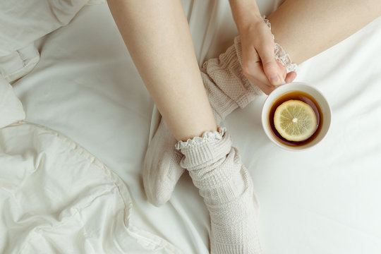 Cozy flatlay of woman's legs in warm white stockings in bed holding cup of lemon tea, selective focus