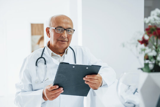Portrait of senior doctor with notepad and in white uniform that stands in the clinic