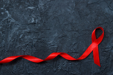 Red ribbon as symbol of aids awareness on black background. Medical care campaign