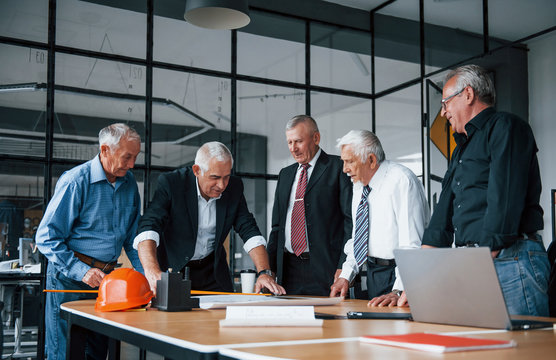 Aged team of elderly businessman architects works with plan in the office