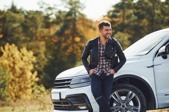 Man in black leather jacket stands near his parked white car outdoors and waits for help